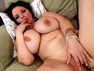 Fat brunette Joanna Bliss poses on sofa