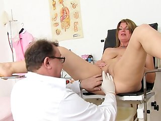 Mature is sitting in medical chair with spread legs